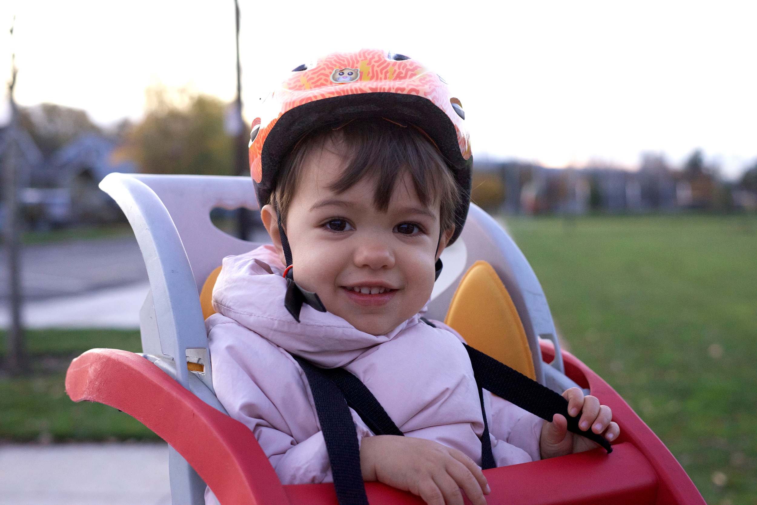 Child wearing a bike helmet and sitting on a bike